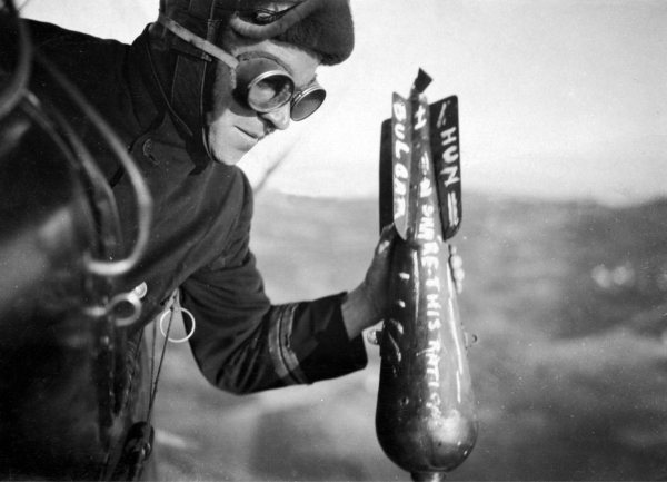 Un aviatore britannico lancia con la mano una bomba sul nemico durante una missione sul Fronte Occidentale. L'abitudine di scrivervi messaggi sopra era frequente durante la Prima Guerra Mondiale. L'utilizzo dell'aviazione in guerra era ancora da perfezionare. Pionieri furono gli italiani durante l'invasione di Libia del 1911 - 1912 - Archivio Top Foto, autore sconosciuto, 1914 – 1918.