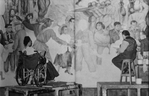 """JUAN GUZMÁN JOHN WOODMAN, FOTOGRAFO NORDAMERICANO CHE TRADUSSO IN SPAGNOLO IL SUO NOME IN """" JUAN GUZMÁN"""" RITRAE FRIDA E DIEGO DAVANTI AL MURALES """"PESADILLA DE GUERRA Y SUEÑO DE PAZ"""". Palazzo delle Belle Arti, Città del Messico, 1952."""