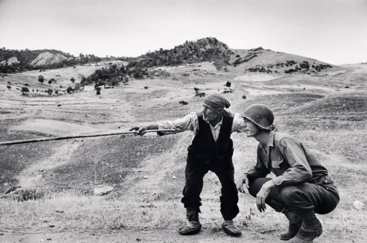Contadino siciliano indica a un ufficiale americano la direzione presa dai tedeschi, nei pressi di Troina, Sicilia, 4-5 agosto 1943 © Robert Capa © International Center of Photography / Magnum Photos