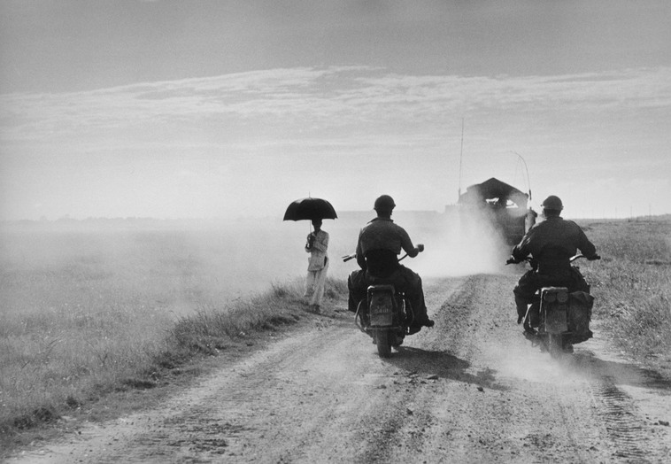 Dei motociclisti e una donna percorrono la strada da Nam Dinh a Thai Binh, Indocina (Vietnam), maggio 1954 © Robert Capa © International Center of Photography / Magnum Photos